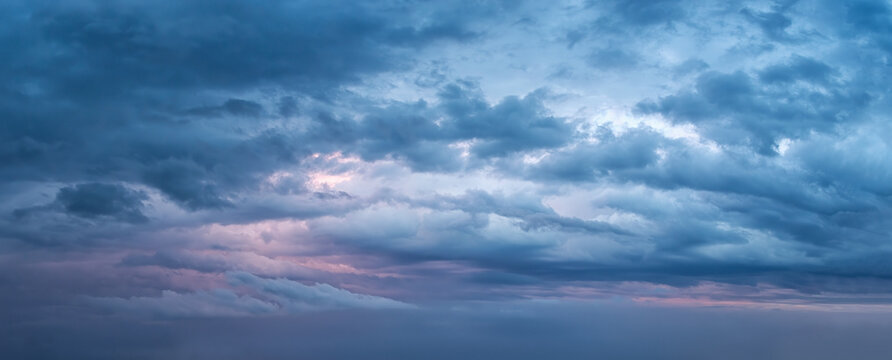 Dramatic overcast sky at evening panoramic shot. Scenic blue gray clouds before the storm. Scenic cloudscape before the rain. Blue hour stormy cloudscape. Dark thunderstorm sky wide image.
