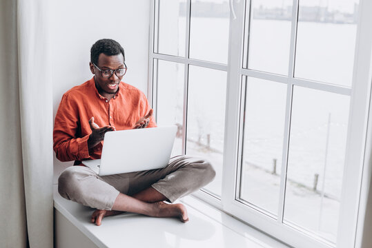 Young african man freelancer in an orange shirt and glasses holds a business meeting with colleagues via video call with a laptop while sitting on the windowsill, a black man conducts an online