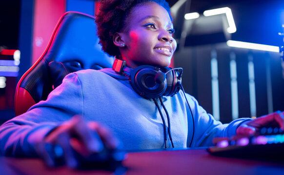 Portrait Gamer African American beautiful woman play online games computer, streamer neon room