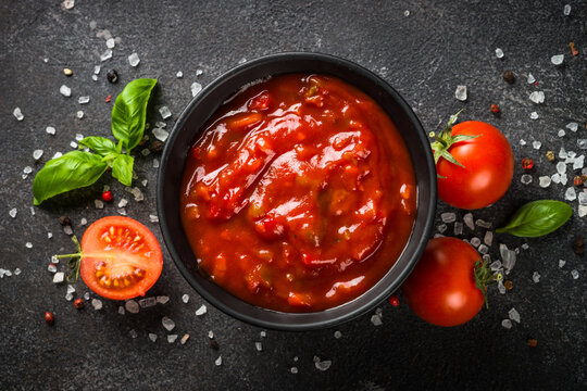 Tomato sauce in a bowl with spices, herbs and fresh tomatoes. Top view at black background.