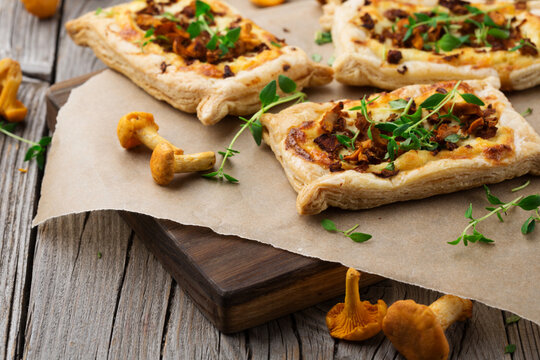 Homemade tarts of puff pastry with seasonal chanterelle mushrooms on rustic table.