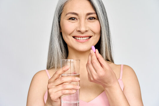 Happy middle aged 50s Asian woman holding pill and glass of water taking dietary supplements. Portrait of smiling adult attractive woman taking care of health in menopause, isolated on white.