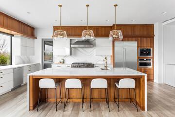 Fototapeta Beautiful kitchen in new luxury home with large waterfall island, gorgeous backsplash and cabinets.   obraz