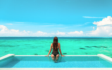 Obraz Swimsuit model relaxing in infinity swimming pool at luxury overwater villa hotel in high end resort. View from the back of sexy woman in black one piece swimsuit enjoying turquoise ocean. - fototapety do salonu