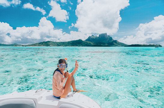 Woman going snorkeling in Bora Bora island, Tahiti, French Polynesia. Happy tourist on luxury vacation getaway on cruise ship luxury yacht private charter swim tour of coral reefs.
