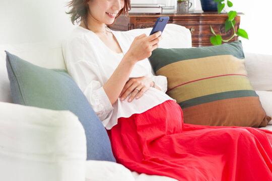 スマートフォンを使っている妊婦の女性