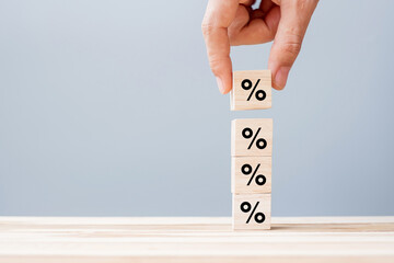business man Hand putting wood cube block with percentage symbol icon. Interest rate,  financial,...
