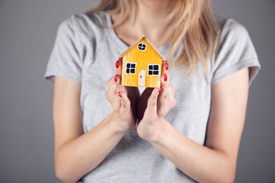 woman holding wooden house model