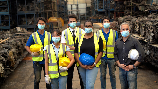 group of diversity Workers wear protective face mask holding hard hat Stand in mourning  together in warehouse industrial factory  during Coronavirus or COVID-19 pandemic. health care in industry