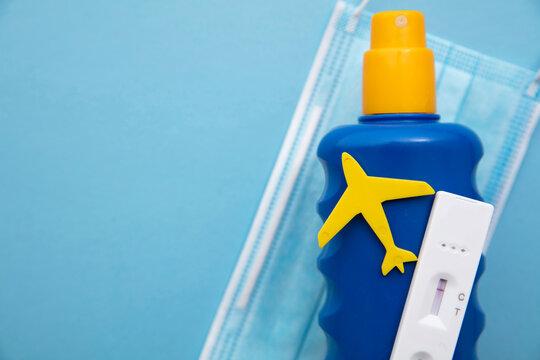 Covid lateral flow test on a bottle of suncream. Coronavirus travel concept