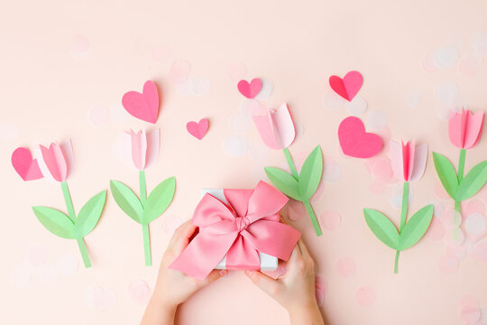 Kids hands holding gift present box with pink bow decorated paper hearts and tulip flowers on pink pastel table top view. Flat lay composition for birthday, valentine, mother day, 8 march, wedding