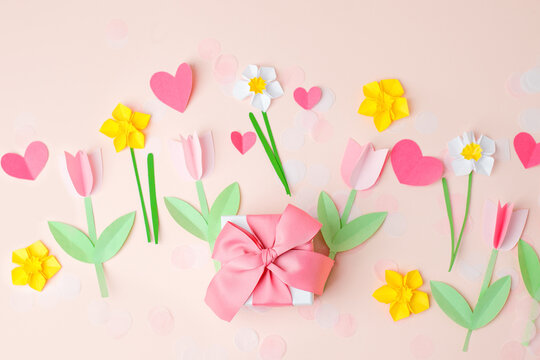 Gift present box with pink bow decorated paper hearts and tulip flowers on pink pastel table top view. Flat lay composition for birthday, valentine, mother day, 8 march, wedding, paper art decor