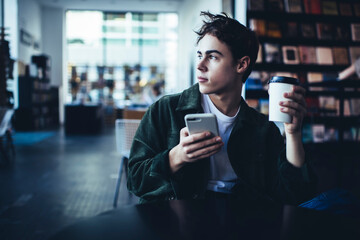 Obraz Pensive man with takeaway coffee using smartphone - fototapety do salonu