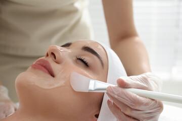 Fototapeta Young woman during face peeling procedure in salon obraz
