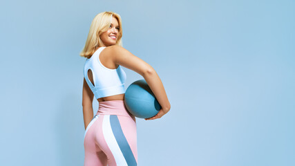 Fototapeta Portrait of a fitness happy fit woman standing holding a medicine ball. Copy Free space for text. Slim caucasian cross fit woman with fitness ball stand in gym, look. Plain light wall background obraz