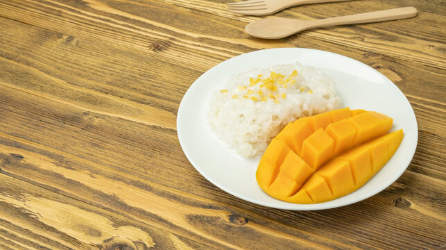Sticky rice and ripe mango (Thai dessert) on a wooden table.