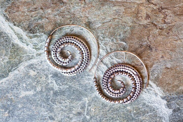 Silver metal decorative oriental spirale design earrings on natural neutral background