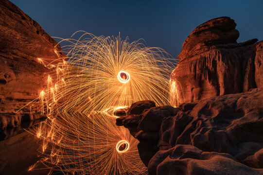 Man wielding rounded burning fire spark from steel wool in rock rapids of grand canyon reflection on river at Hat Chom Dao