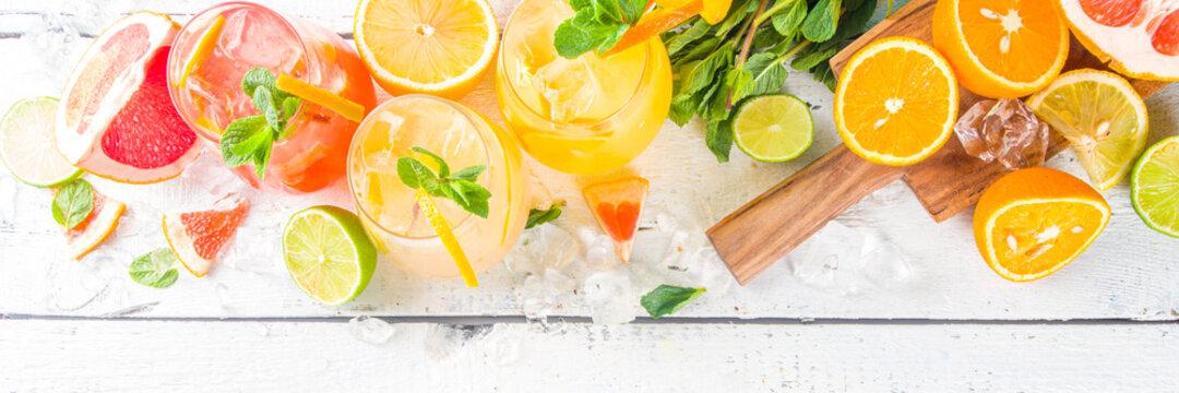 Summer cold drinks, fruit lemonade sangria cocktail, infused beverages with various citrus - orange, lemon, grapefruit, lime, with fresh fruits copy space