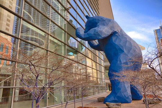 """Denver, CO - March 7, 2021: """"I See What You Mean"""" sculpture created by artist Lawrence Argent in 2005.  The Big Blue Bear, as it is often called, peaks into the windows of the Denver Convention Center"""