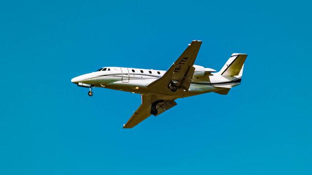 Beautiful small jet airplane (YR-TYA) approaching munich airport MUC on a sunny winter day