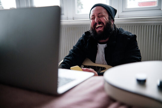 Mature man with laptop laughing at home