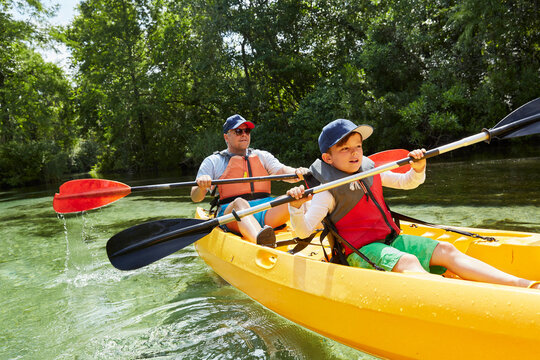 Boy with father in life jacket canoeing with oar in lake during picnic