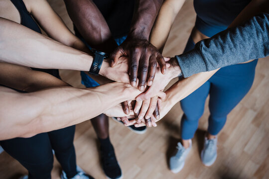 Multi-ethnic group of friends huddling while standing in gym