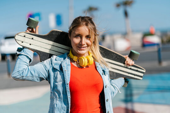 Beautiful blond woman holding longboard on shoulder during sunny day