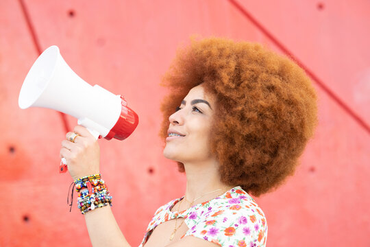 Smiling woman with megaphone by red wall