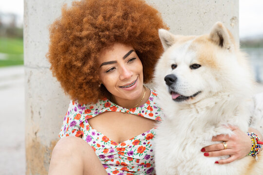 Smiling woman looking at fluffy dog