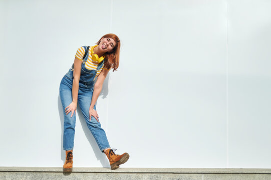 Young woman sticking out her tongue while standing in front of white wall