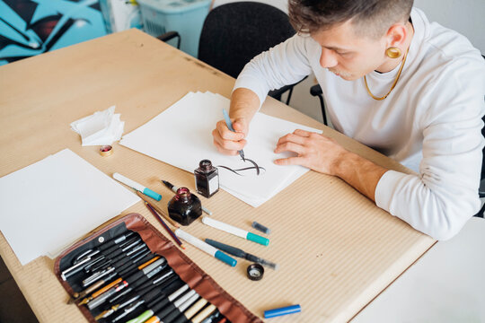 Hipster young man practicing calligraphy on paper in studio
