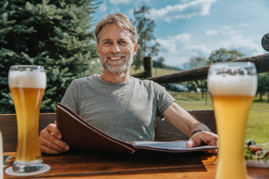 Smiling bearded man holding menu while sitting in beer garden