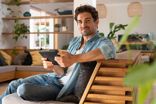 Handsome man with digital tablet sitting on couch in living room