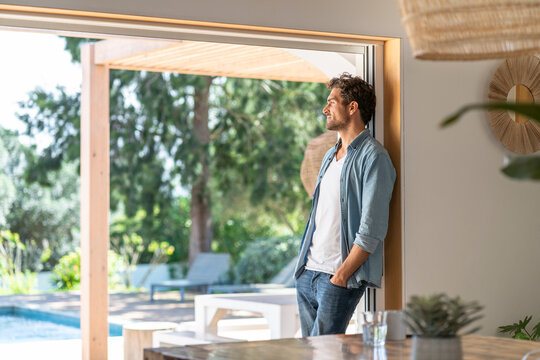 Thoughtful man with hands in pockets leaning on doorframe at home