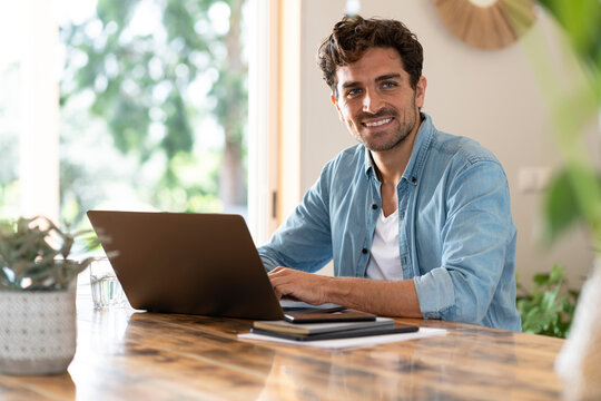 Smiling male freelancer looking away while sitting with laptop at home office