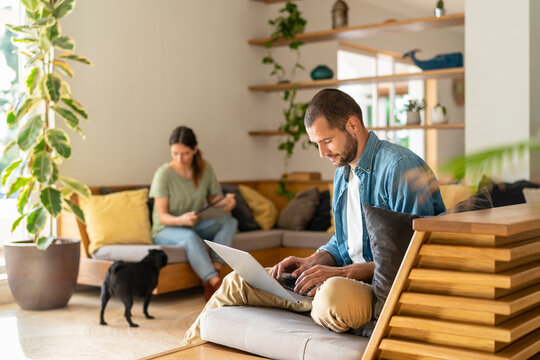 Young man working on laptop while wife looking at Pug dog in background at home