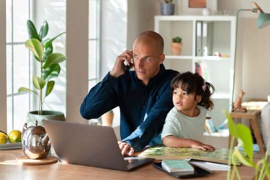 Father talking on mobile phone while sitting with daughter in home office