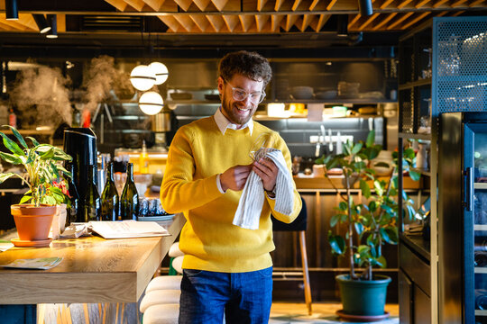 Smiling male cafe owner cleaning wineglass at cafe