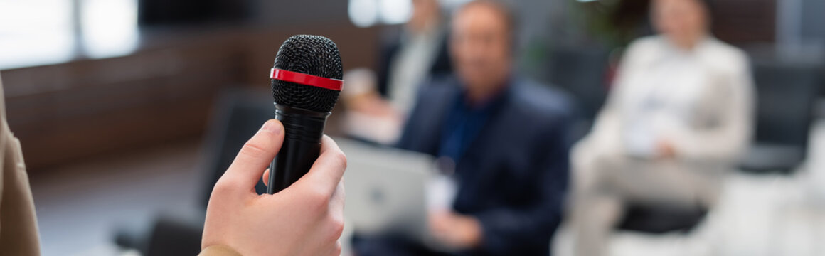lecturer holding microphone near blurred audience during seminar, banner