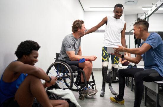 Happy male amputee and paraplegic athletes in locker room