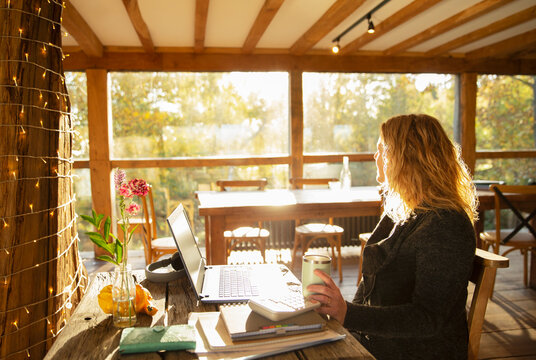 Thoughtful businesswoman working at laptop in sunny restaurant