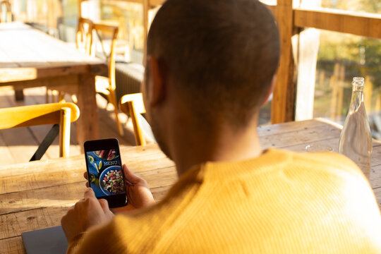 Male business owner looking at restaurant menu on smart phone