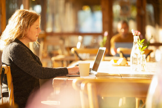 Businesswoman with coffee working at laptop in sunny cafe