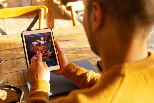 Man with digital tablet ordering food by app on digital tablet