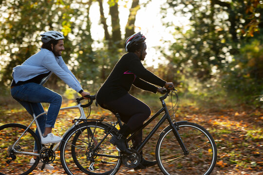 Friends riding bicycles through autumn leaves in park