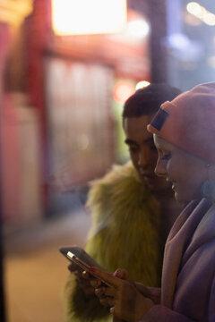 Stylish young couple using smart phones on urban sidewalk