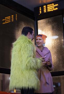 Stylish young couple waiting at bus stop at night