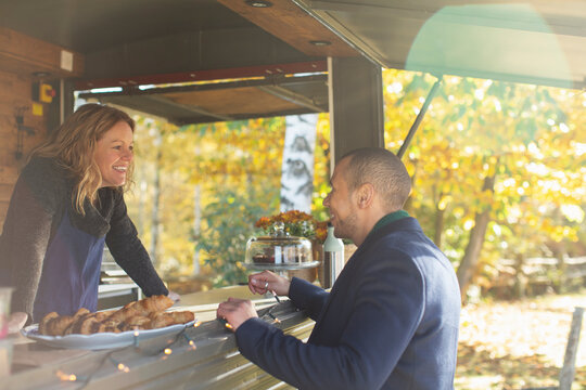 Happy friendly food cart owner talking with customer in autumn park